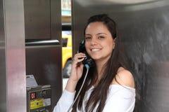 Muchacha bonita que habla por el teléfono público Imagen de archivo