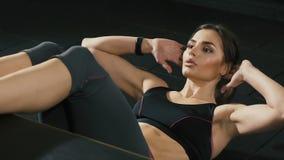Muchacha bonita que hace ejercicios en el gimnasio, haciendo pectorales del ABS almacen de video