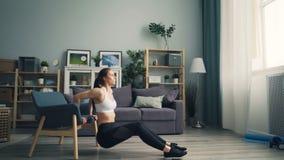 Muchacha bonita que hace inmersiones de la flexión de brazos en casa usando el entrenamiento de la butaca en el apartamento solam almacen de metraje de vídeo