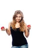 Muchacha bonita que hace juegos malabares dos manzanas rojas Imagen de archivo