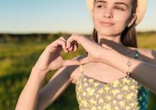 Muchacha bonita que hace las manos en forma del corazón al aire libre Imagenes de archivo