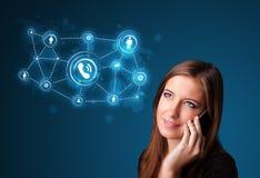 Muchacha bonita que hace llamada de teléfono con los iconos sociales de la red Foto de archivo libre de regalías