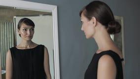Muchacha bonita que hace maquillaje en mirada del cuarto de baño en el espejo La mujer toma cuidado sobre mirada mirada en un esp almacen de metraje de vídeo