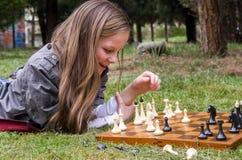 Muchacha bonita que juega a ajedrez foto de archivo