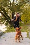 Muchacha bonita que juega con el perro durante paseo en el parque al aire libre fotografía de archivo