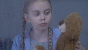 Muchacha bonita que juega con soledad sufridora del peluche-oso preferido y que tiraniza almacen de video