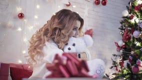 Muchacha bonita que juega con un juguete del oso de peluche que se sienta en una cama cerca de un árbol de navidad metrajes