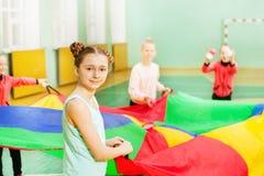 Muchacha bonita que juega a juegos del paracaídas en pasillo de deportes Foto de archivo