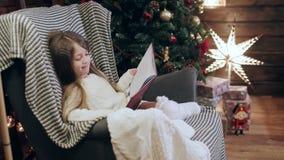 Muchacha bonita que lee un libro cerca de un árbol de navidad almacen de metraje de vídeo