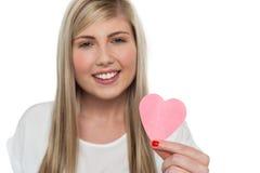 Muchacha bonita que lleva a cabo el corazón de papel rosado lindo Foto de archivo libre de regalías