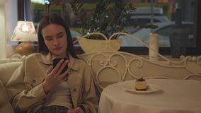 Muchacha bonita que manda un SMS en su teléfono móvil que se sienta en la tabla en el restaurante El pedazo de torta sabrosa está metrajes