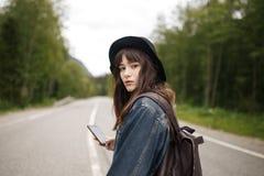 Muchacha bonita que manda un SMS en su teléfono mientras que camina al lado del camino ocupado Imágenes de archivo libres de regalías