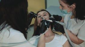 Muchacha bonita que miente en silla dental en el tratamiento 4K almacen de metraje de vídeo