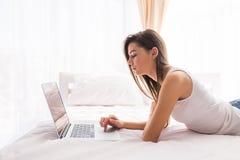 Muchacha bonita que mira el monitor del ordenador portátil mientras que miente en cama Fotos de archivo libres de regalías