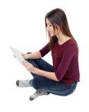 Muchacha bonita que mira su tableta Foto de archivo libre de regalías