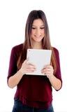 Muchacha bonita que mira su tableta Fotos de archivo