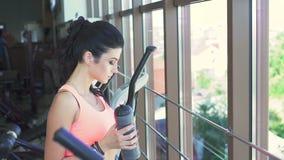 Muchacha bonita que mira a través de la ventana y del agua potable en el gimnasio lentamente almacen de metraje de vídeo