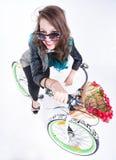 Muchacha bonita que monta una bici que sonríe - en el fondo blanco Fotografía de archivo