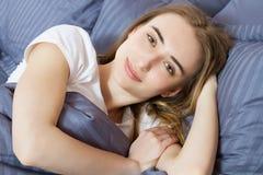 Muchacha bonita que pone en cama, hembra preciosa de la sonrisa que presenta en un dormitorio imagen de archivo