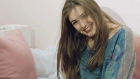 Muchacha bonita que presenta a la cámara con emociones en el fondo de la cama lentamente metrajes