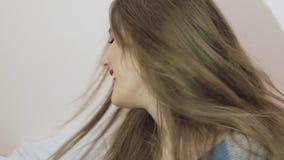 Muchacha bonita que presenta a la cámara con emociones y pelo que lanza lentamente almacen de video