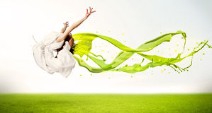 Muchacha bonita que salta con el vestido líquido abstracto verde Imágenes de archivo libres de regalías