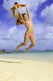 Muchacha bonita que salta en la playa Fotografía de archivo