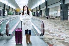 Muchacha bonita que se coloca en el vestíbulo del aeropuerto Imágenes de archivo libres de regalías
