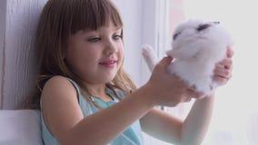 Muchacha bonita que se divierte, abrazando y jugando con el conejo decorativo almacen de video