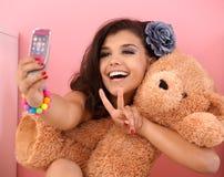 Muchacha bonita que se fotografía y el oso del juguete Imagen de archivo libre de regalías