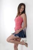 Muchacha bonita que se inclina contra la pared blanca Foto de archivo libre de regalías