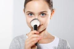 Muchacha bonita que se pulveriza la nariz Foto de archivo libre de regalías