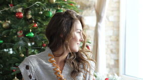 Muchacha bonita que se sienta cerca de decoraciones de la Navidad y que mira a un lado lentamente almacen de video