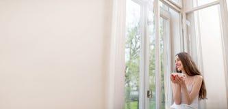 Muchacha bonita que se sienta cerca de la ventana y que mira hacia fuera la ventana w Fotos de archivo libres de regalías