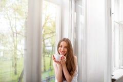 Muchacha bonita que se sienta cerca de la ventana y que mira los wi de la cámara Imágenes de archivo libres de regalías