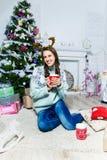 Muchacha bonita que se sienta cerca del árbol de navidad en un cuarto blanco Imágenes de archivo libres de regalías