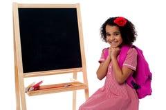Muchacha bonita que se sienta cerca del tablero de tiza en blanco Imagen de archivo libre de regalías
