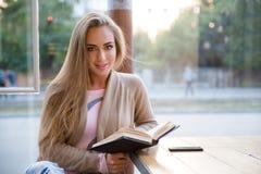 Muchacha bonita que se sienta con el libro en café Fotografía de archivo libre de regalías