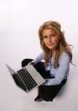 Muchacha bonita que se sienta con el ordenador portátil Imagenes de archivo