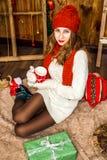 Muchacha bonita que se sienta con los regalos de la Navidad Fotos de archivo