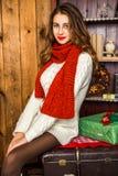 Muchacha bonita que se sienta con los regalos de la Navidad Imagenes de archivo