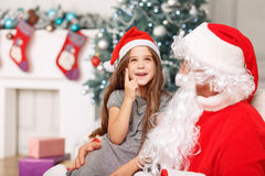 Muchacha bonita que se sienta con Papá Noel Fotos de archivo