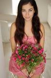 Muchacha bonita que se sienta con un ramo de flores en dre floral rosado Imagen de archivo libre de regalías