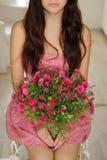 Muchacha bonita que se sienta con un ramo de flores en dre floral rosado Foto de archivo libre de regalías