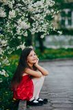 Muchacha bonita que se sienta debajo del cerezo Imagen de archivo