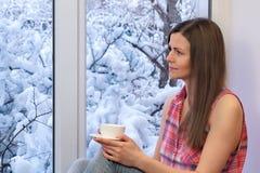 Muchacha bonita que se sienta en el alféizar, mirando la ventana y bebiendo el café Invierno afuera Imagen de archivo