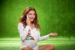 Muchacha bonita que se sienta en el teléfono que habla de la hierba, atractivo joven Fotografía de archivo