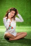 Muchacha bonita que se sienta en el teléfono que habla de la hierba, atractivo joven Foto de archivo