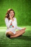 Muchacha bonita que se sienta en el teléfono que habla de la hierba, atractivo joven Imagen de archivo