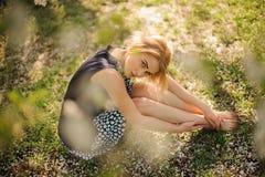 Muchacha bonita que se sienta en la hierba en parque Fotos de archivo